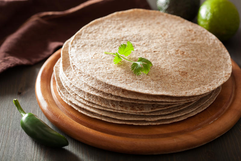 Whole wheat tortillas on wooden board and vegetables stock image