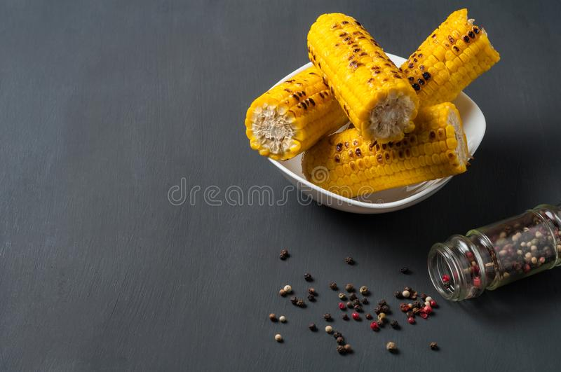 Whole white ceramic plate full of fried corn cobs near scattered pepper lies on dark concrete table stock image