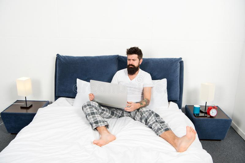 Whole world in his laptop. Man surfing internet or working online. Hipster bearded guy pajamas freelance worker. Remote stock images