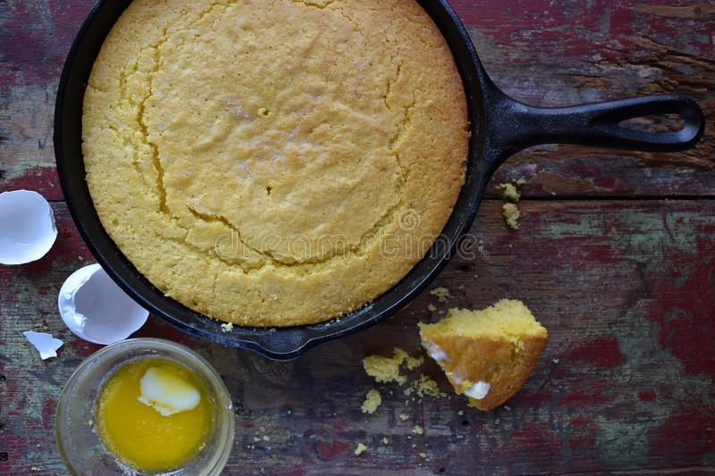Whole Yellow Cornbread in cast iron skillet on rustic wood table top view stock images