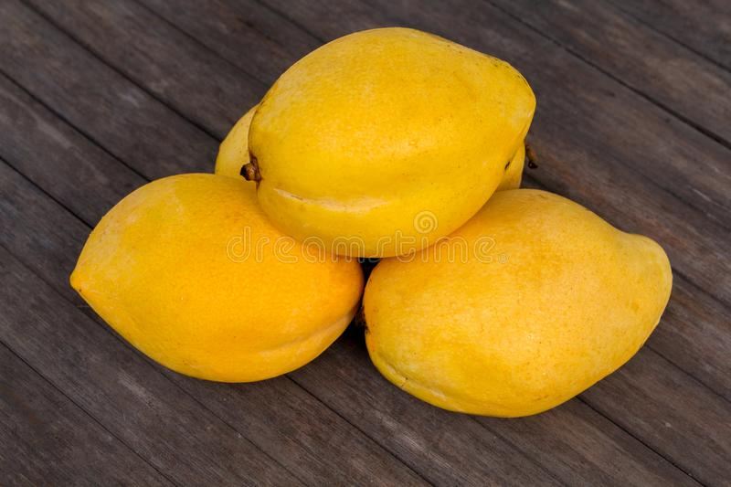 Whole yellow mango on wooden background. Bunch of tropical fruits. royalty free stock photos
