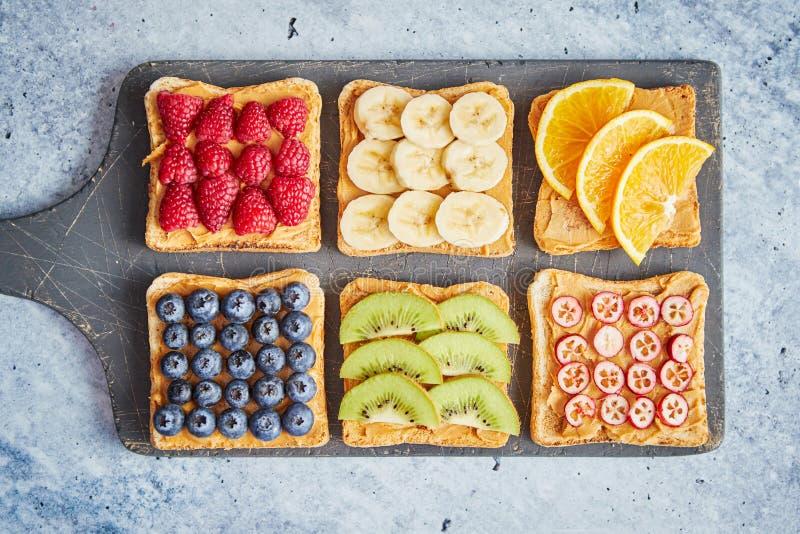 Wholegrain куски хлеба с арахисовым маслом и различными плодами стоковое фото rf