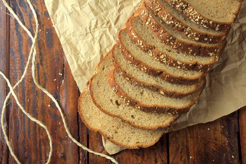 Wholegrain skivade organiskt bröd som komponerades av havre och linfrö på trätabellen, på papper banta sunt arkivbild