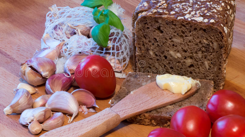 Wholemeal bread butter tomatoes and garlic stock images