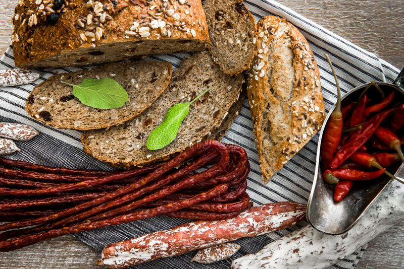 Wholemeal bread with dried sausages. On a table stock photos