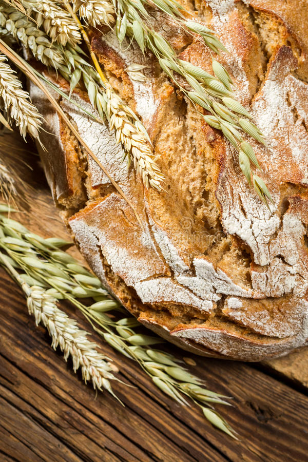 Wholemeal bread on old wooden table royalty free stock images