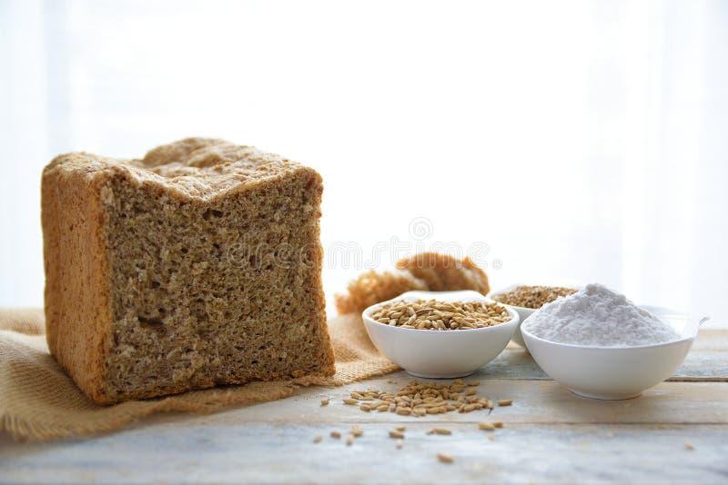 Wholemeal chleb na burlap tkaninie obok niektóre zboży przeciw białemu tłu i mąki zdjęcia royalty free