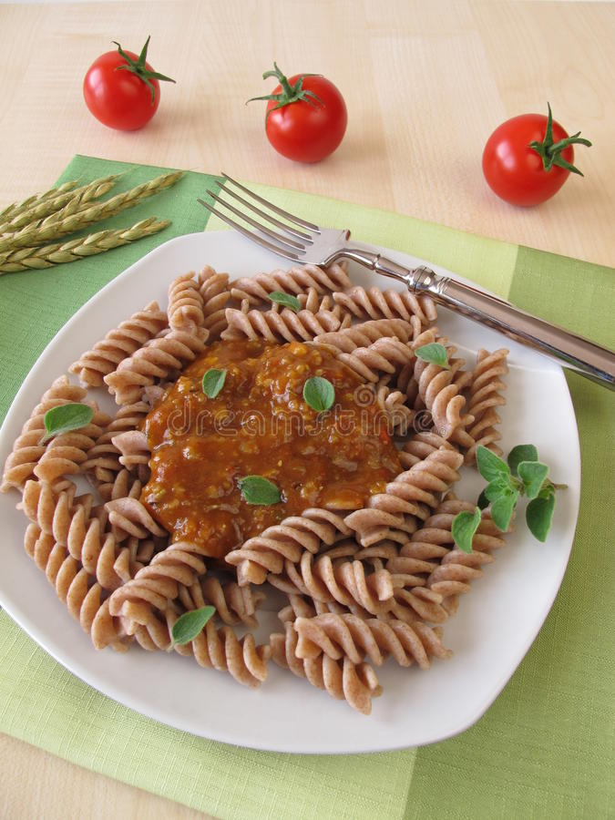Wholemeal pasta with green core bolognese. And fresh tomatoes stock photo