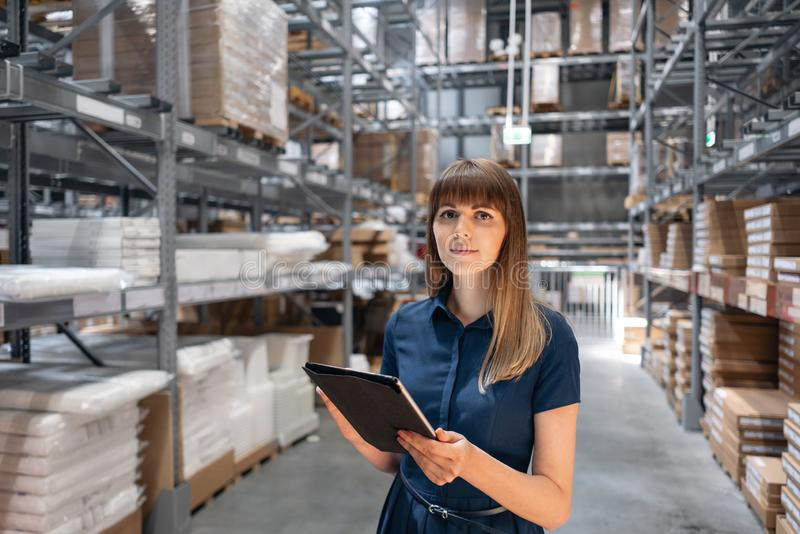 Wholesale warehouse. Beautiful young woman worker of store in shopping center. Girl looking for goods with a tablet is royalty free stock photo