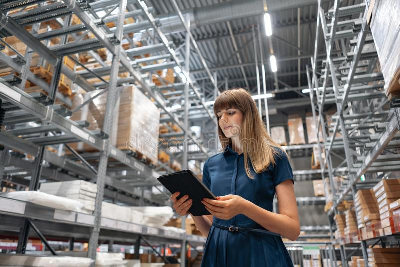 Wholesale warehouse. Beautiful young woman worker of store in shopping center. Girl looking for goods with a tablet is royalty free stock images