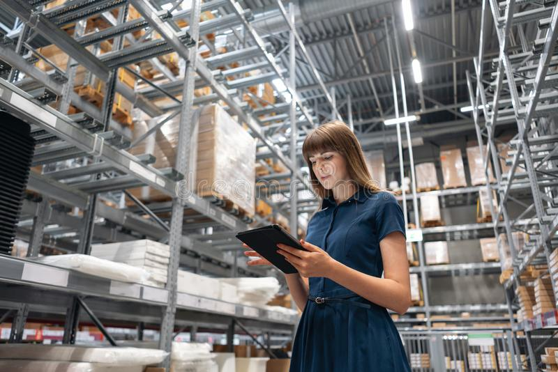 Wholesale warehouse. Beautiful young woman worker of store in shopping center. Girl looking for goods with a tablet is stock photo