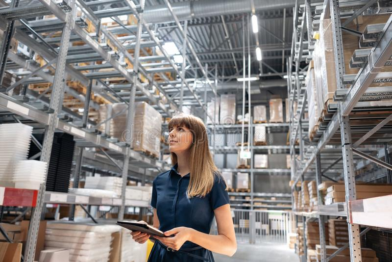 Wholesale warehouse. Beautiful young woman worker of store in shopping center. Girl looking for goods with a tablet is stock photography