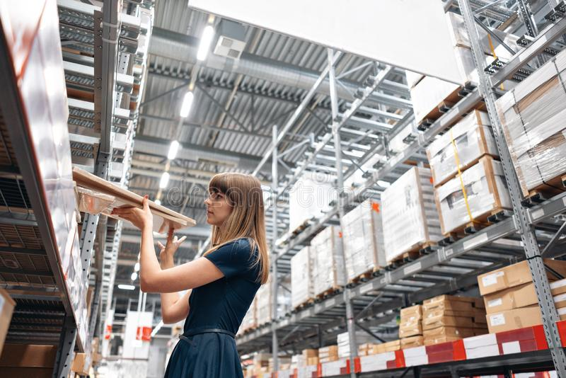 Wholesale warehouse. Beautiful young woman worker of store in shopping center. Girl looking for goods with a tablet is stock photos