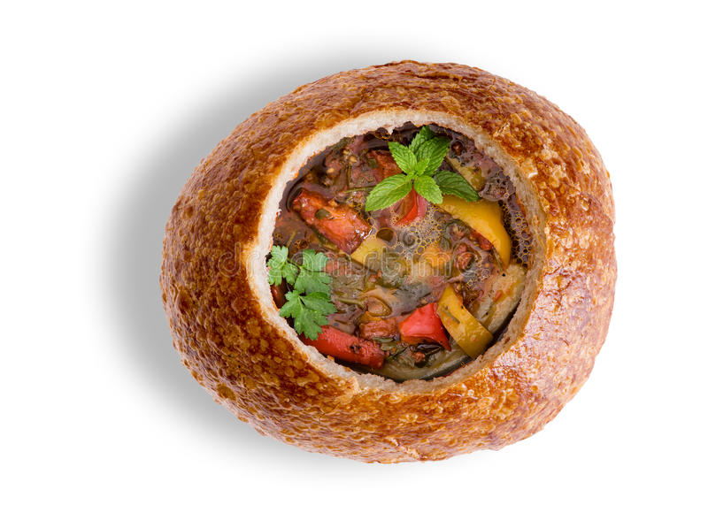 Wholesome vegetable soup in a sourdough bread bowl. Wholesome vegetable soup with eggplant, brinjal or aubergine, in a sourdough bread bowl garnished with fresh stock photo