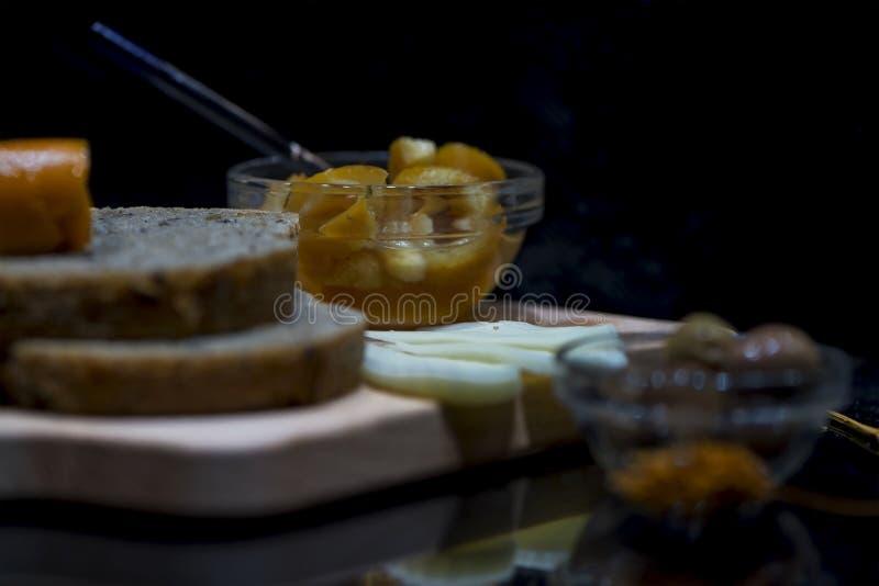 Wholewheat chleby z serem, dżemami i zielonymi oliwkami na drewnianej ciapanie desce z ich odbiciami, zakończenie w górę, makro- zdjęcie stock