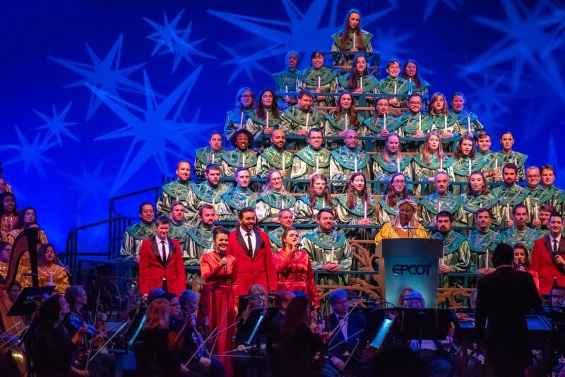 Whoopi Goldberg vertelt het ontroerende verhaal van Kerstmis, vergezeld van orkest en hevig koor in Candlelight Narrators op E stock fotografie
