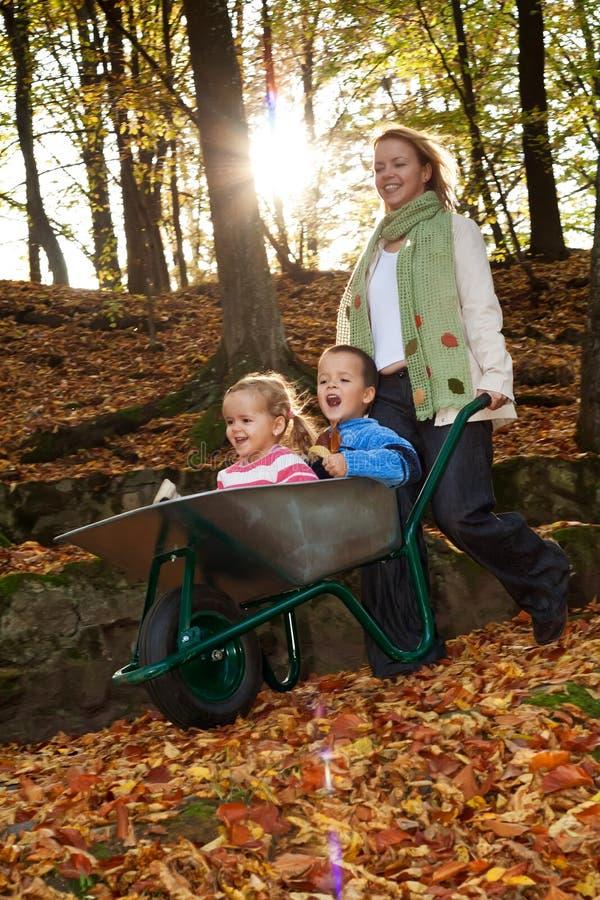 Whooshing through autumn. Kids in wheelbarrow, slight motion blur