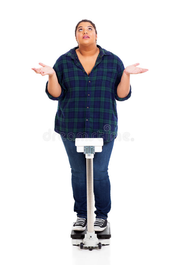 Why?. Overweight young woman asking why when weighting herself stock image