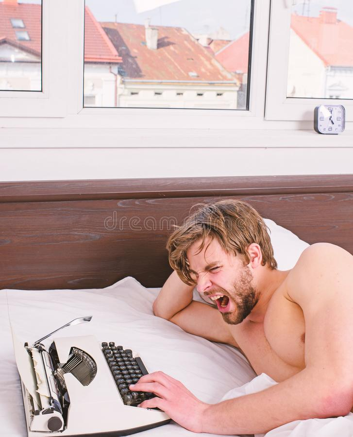 Why author use manual typewriter daily work. Man writer lay bed white bedclothes working on new book. Writer author used. Old fashioned machine instead of royalty free stock images