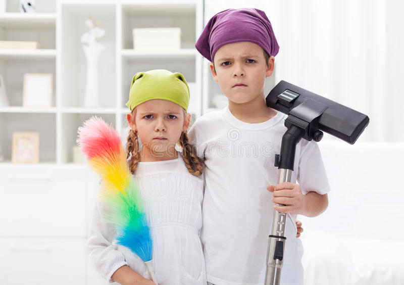 Why do we have to clean our room. Upset kids with cleaning utensils royalty free stock photo