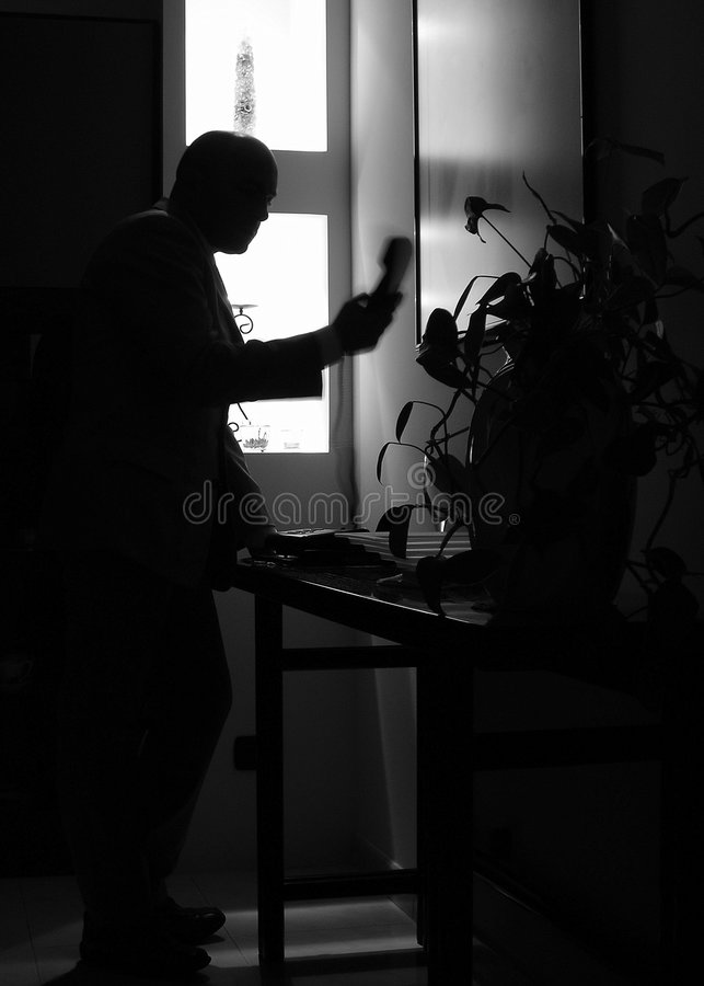 Why doesn't she answer? - B&W. Man angry after phoning late at night... - back lit royalty free stock photos