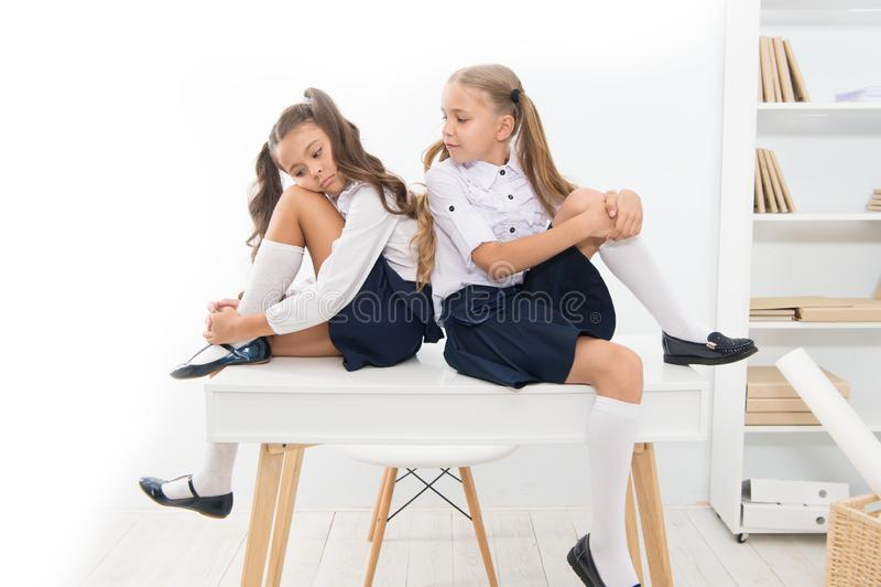 Why are you sad. School club. Little schoolgirls classmates friendly kids. Schoolgirls friends sit on desk. Best friends. Relaxing. Schoolgirls tidy hairstyle stock photos