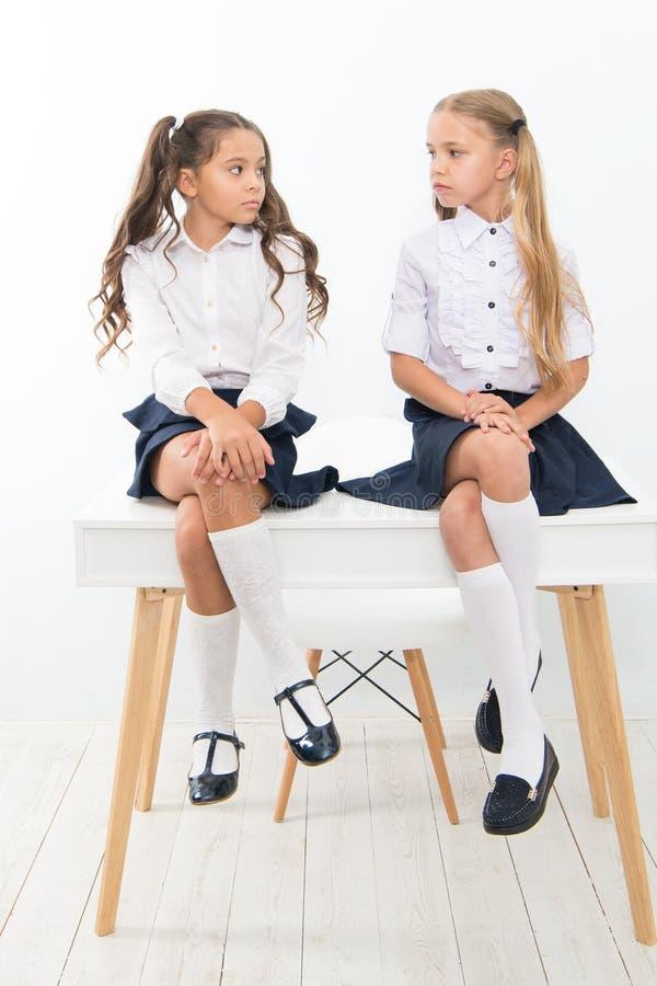 Why are you sad. Schoolgirls tidy hairstyle relaxing having rest. School uniform. School club. Little schoolgirls. Classmates friendly kids. Schoolgirls friends stock image