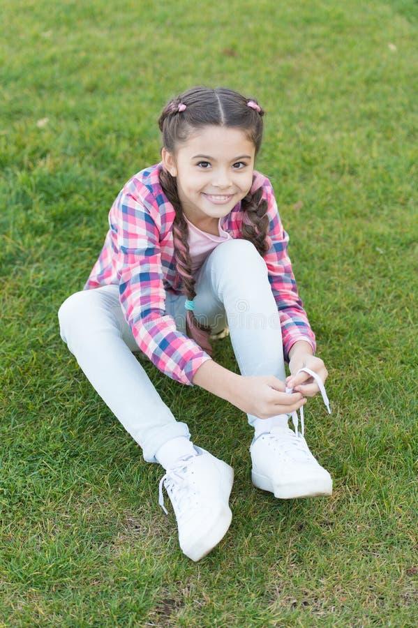 Wiązać shoelaces Dziewczyny małe dziecko wydaje czas wolnego outdoors w parku Dziewczyna siedzi na trawie w parku Dziecko cieszy  obrazy stock