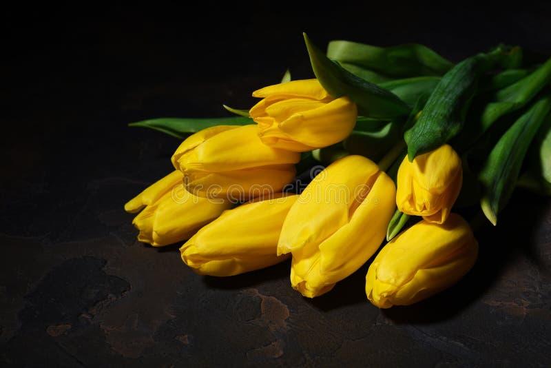 Wiązka żółci tulipany na ciemnym tle zdjęcia stock