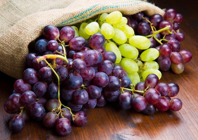 Wiązek czarni i zieleni winogrona na drewnianym obrazy royalty free