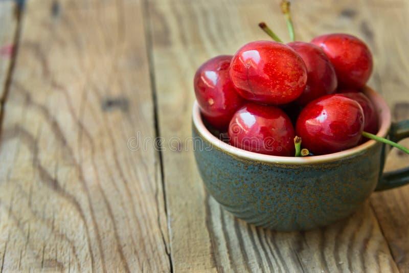 Wiązka świeże dojrzałe kolorowe glansowane słodkie wiśnie w ceramicznej herbacianej filiżance na drewnianym tle, minimalista, kop obraz stock