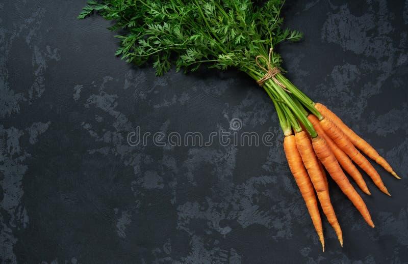 Wiązka świeże marchewki na czarnym tle, odgórny widok obraz stock