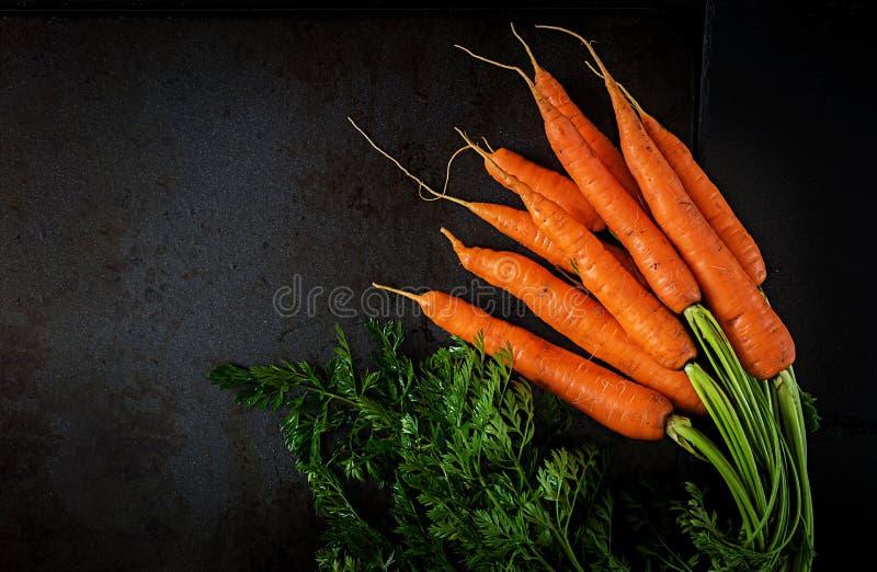 Wiązka świeże marchewki z zielenią opuszcza na ciemnym tle Mieszkanie nieatutowy Odgórny widok zdjęcia stock
