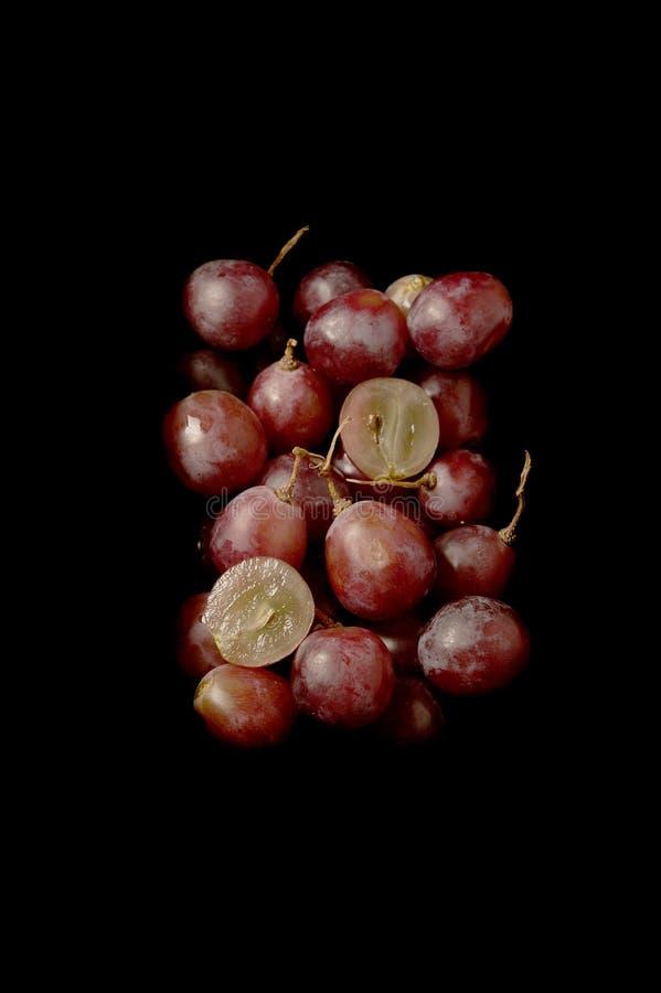 Wiązka świezi czerwoni winogrona nad czarnym tłem fotografia royalty free