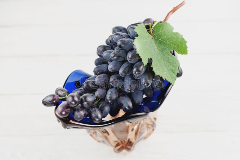Wiązka świezi dojrzali błękitni winogrona z zielonym liściem w szklanej wazie na starym drewnianym bielu zaszaluje fotografia stock