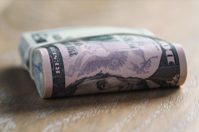 Wiązka dolary na dębowego drewna stole fotografia stock