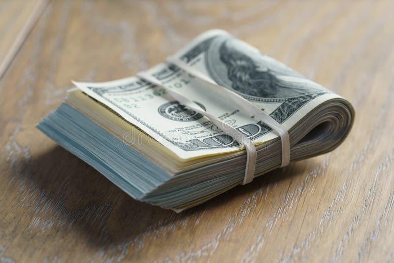 Wiązka dolary na dębowego drewna stole zdjęcie stock