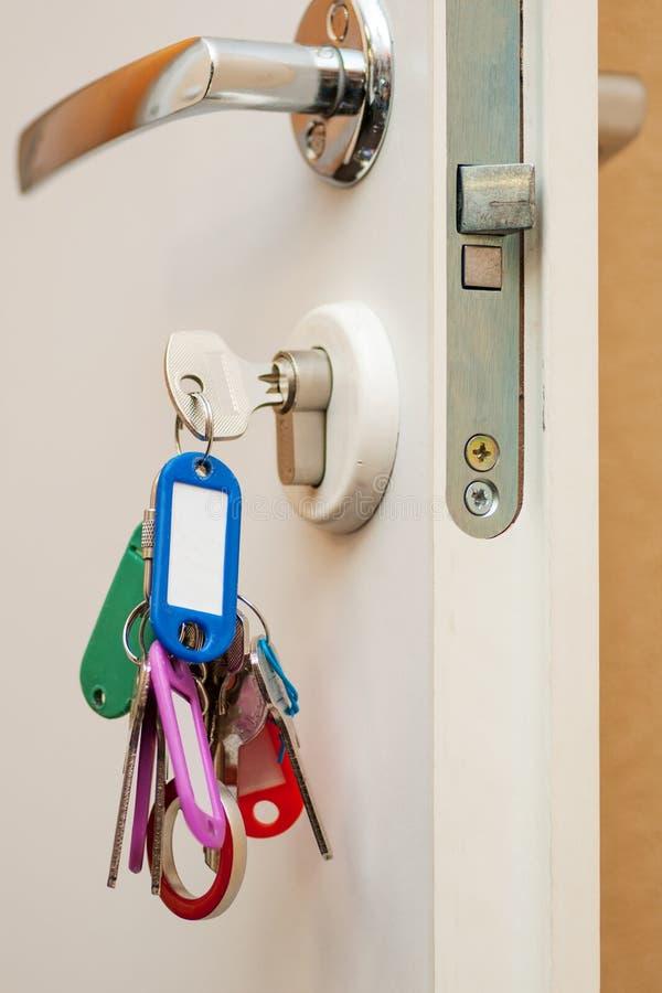 Wiązka klucze i keychains w keyhole otwarte drzwi zdjęcie royalty free