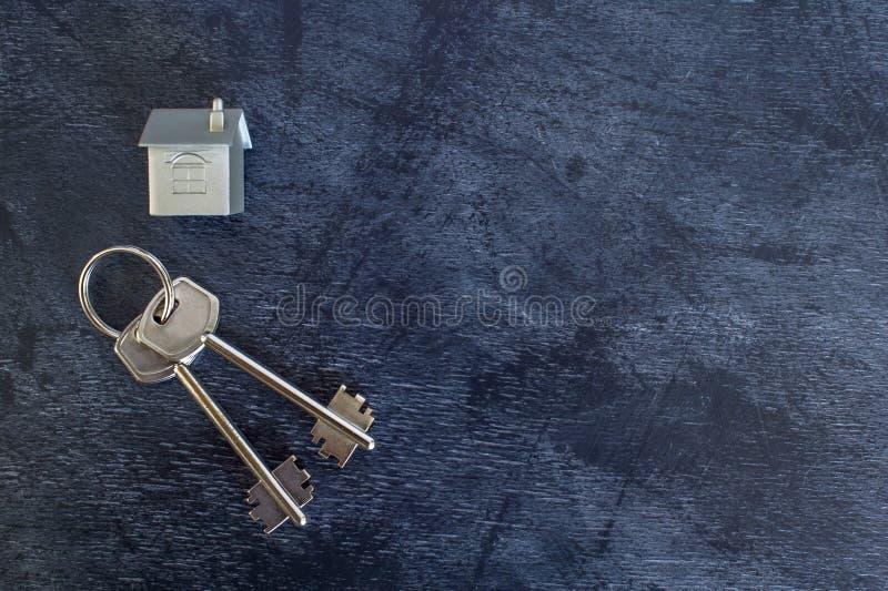 Wiązka klucze kłama na rocznika ciemnym tle wraz z imitacją dom w postaci metalu układu zdjęcia royalty free