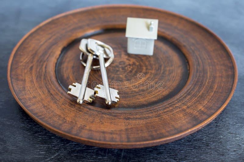 Wiązka klucze kłama na rocznika talerzu, wraz z imitacją dom w postaci metalu układu fotografia royalty free