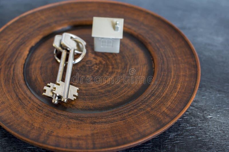Wiązka klucze kłama na rocznika talerzu, wraz z imitacją dom w postaci metalu układu zdjęcie royalty free