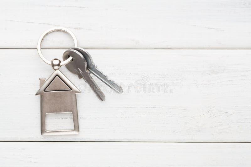 Wiązka klucze z domem kształtował keychain na białym drewnie zdjęcie stock