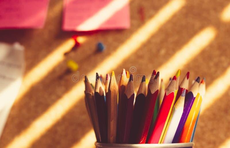 Wiązka kolorowi ołówki w właścicielu przed korek deską zdjęcia stock