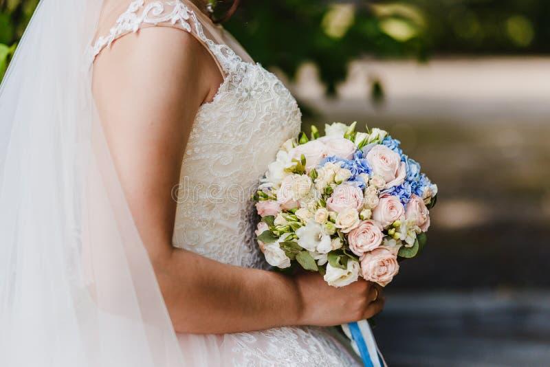 Wiązka małe różowe i błękitne róże w rękach panna młoda zdjęcia royalty free