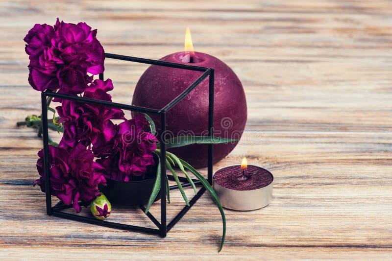 Wiązka purpurowi goździki i zaświecać świeczki obraz stock