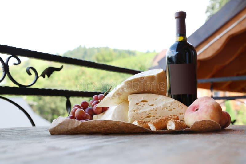 Wiązka winogrona, wino, ser i brzoskwinie na drewnianym stole, obraz royalty free