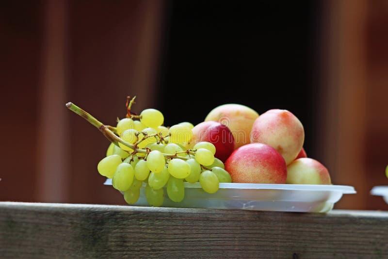 Wiązka zieleni winogrona i brzoskwinie na talerzu zdjęcie stock