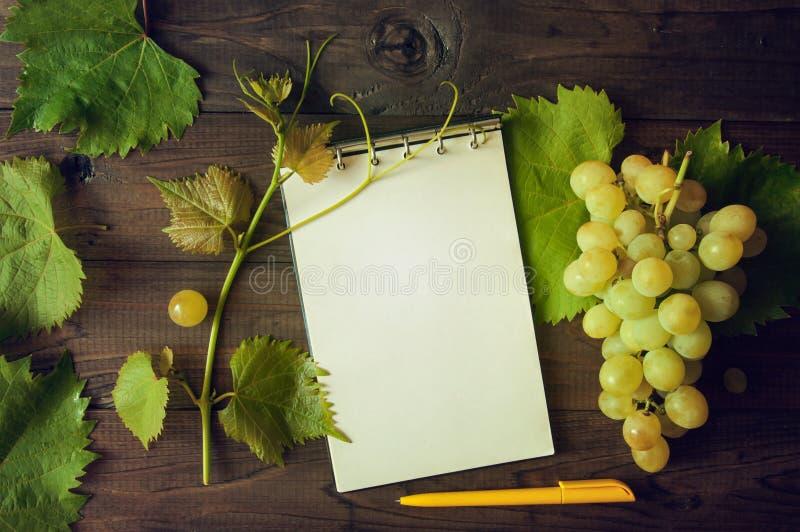 Wiązka zieleni winogrona z liśćmi, notatnikiem i piórem na drewnianym tle, obrazy royalty free
