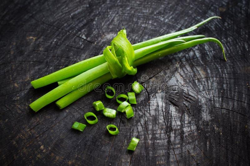 Wiązka zielone cebule na ciemnym tle obraz stock