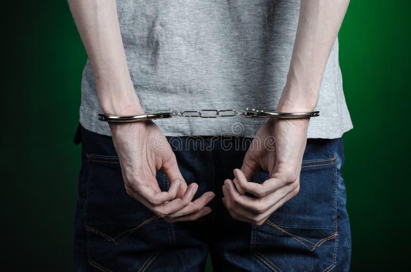 Więźniarski i skazujący temat: mężczyzna z kajdankami na jego rękach w szarej koszulce i niebieskich dżinsach na ciemnozielonym t fotografia royalty free